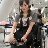 A 19-year-old woman nicknamed Miyu shows off a bag designed for women who use wheelchairs. The bag can be hooked to a wheelchair using a specially designed belt. | KYODO