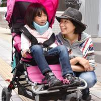 Akari Kojima sits on a stroller for people with disabilities, accompanied by her mother, Yayoi, in Adachi Ward, Tokyo, in June. | KYODO
