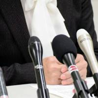 A plaintiff speaks during a news conference Wednesday after her claim against the state over the right to file a lawsuit concerning legal fatherhood of a child was dismissed. | KYODO