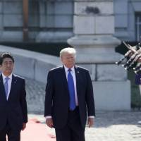 U.S. President Donald Trump and Prime Minister Shinzo Abe review an honor guard during a welcome ceremony at Akasaka Palace in Tokyo on Monday. | AP