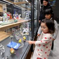 Children look at plastic models displayed at Gundam Base Tokyo in the Diver City Tokyo commercial complex on Oct. 14. | YOSHIAKI MIURA