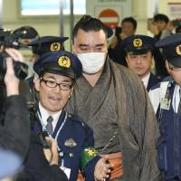 Harumafuji is escorted by police at Haneda airport Thursday evening after returning to tokyo from Fukuoka. | KYODO