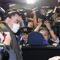 Sumo Grand Champion Harumafuji is mobbed by reporters as he gets into a vehicle after arriving at Tokyo's Haneda airport on Thursday. | KYODO