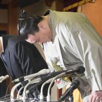 Harumafuji and his stablemaster, Isegahama, bow during a news conference Wednesday in Dazaifu, Fukuoka Prefecture. | KYODO