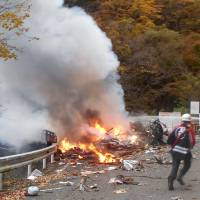 A helicopter is seen after it crashed and burst into flames in the village of Ueno, Gunma Prefecture, on Wednesday. | COURTESY OF A LOCAL RESIDENT / VIA KYODO