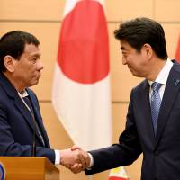 Philippine President Rodrigo Duterte shakes hands with Prime Minister Shinzo Abe after a meeting at Abe's official residence in Tokyo on Oct. 30. | REUTERS