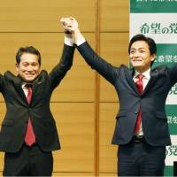 Yuichiro Tamaki (right), a Lower House lawmaker selected as co-leader of the opposition Party of Hope (Kibo no To), and his sole rival, Hiroshi Ogushi, raise their hands on Friday. | KYODO