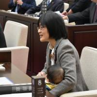 Yuka Ogata, a Kumamoto city lawmaker, is seen bringing her 7-month-old baby son to assembly meeting last week. | KYODO