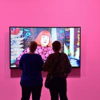 Women watch a video of artist Yayoi Kusama at her 'Infinity Mirrors' exhibition at The Broad contemporary museum in Los Angeles on Friday. | KYODO