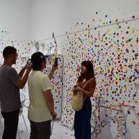 Visitors take photos in a gallery at the 'Yayoi Kusama: Infinity Mirrors' exhibition, at The Broad contemporary museum in Los Angeles on Friday. | KYODO