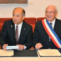 Masaomi Tokuta (left), mayor of Sagara, Kumamoto Prefecture, and Pierre Rousseau, mayor of Saint-Valentin, France, attend a signing ceremony in Paris on Friday. The two villages formed a sister-city relationship, each relying on 'love' to boost their economy. | KYODO