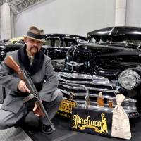 Kazuhiko Kurita, dressed in a vintage suit with his replica Tommy gun, poses for a photo next to his 1947 Chevrolet Fleetline, at the Lowrider Super Show held in Makuhari Messe in Chiba Prefecture earlier this month.   YOSHIAKI MIURA