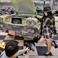 A model poses for a photo beside a customized car at the Lowrider Super Show in Makuhari Messe earlier this month.   YOSHIAKI MIURA
