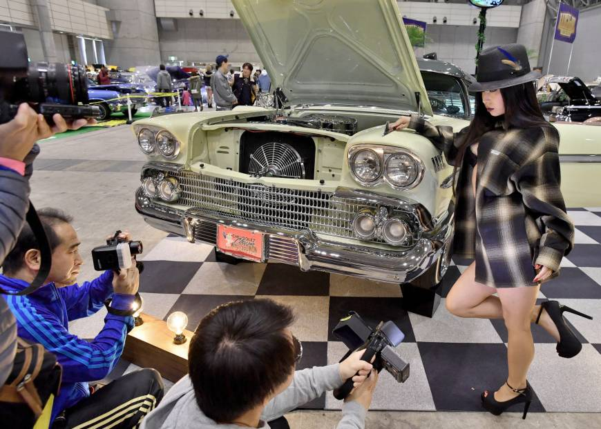 A model poses for a photo beside a customized car at the Lowrider Super Show in Makuhari Messe earlier this month.