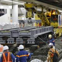 A railroad crane hauls girders early Saturday for a maglev platform under construction beneath Shinagawa Station in Tokyo. Magnetically levitated trains are finally expected to enter service as the fastest in the nation after Central Japan Railway Co. (JR Tokai) completes the Chuo Shinkansen Line between Tokyo and Nagoya in 2027. | KYODO