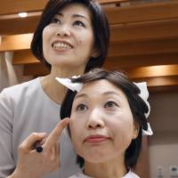 Maki Tsunoda, 56, receives makeup advice to conceal a skin disorder brought on by cancer treatment, during a visit to the Shiseido Life Quality Beauty Center in Tokyo's Ginza district on Oct. 27. | KYODO