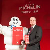 Nihon Michelin Tire Co. CEO Paul Perriniaux poses with a corporate mascot Tuesday in Tokyo during a news conference to launch the Michelin Guide Tokyo 2018.   COURTESY OF MICHELIN