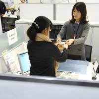 My Number identification documents are distributed at the Itabashi Ward Office in Tokyo in January 2016. | KYODO
