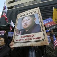 An anti-North Korea protester holds up a portrait of the country's leader, Kim Jong Un, during a rally welcoming U.S. President Donald Trump near the U.S. Embassy in Seoul on Nov. 6. | AP