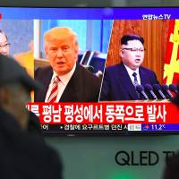 Pedestrians at a railway station in Seoul on Wednesday watch a television news program showing pictures of U.S. President Donald Trump and North Korean leader Kim Jong Un. | AFP-JIJI