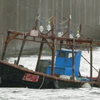 A wooden boat that washed ashore Thursday night in the city of Yurihonjo, Akita Prefecture, is seen on Friday. Police said eight men found aboard the vessel claim they are from North Korea. | KYODO