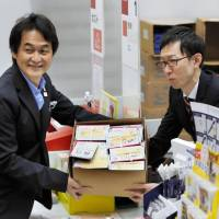 Takeshi Natsuno (left), a member of the panel choosing the mascot for the Tokyo Olympics, displays a box of postcards Monday with information on the voting process to be sent to elementary schools nationwide. | POOL / VIA KYODO