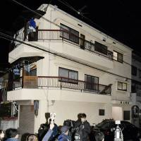 Members of the media gather in front of an apartment building late Monday in Neyagawa, Osaka Prefecture, where the bodies of four newborns were found in buckets filled with cement. | KYODO