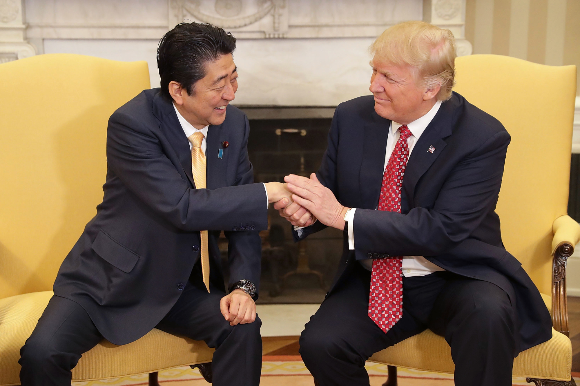 Prime Minister Shinzo Abe shakes hands with U.S. President Donald Trump at the White House in February in Washington. | KYODO