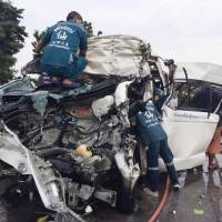 Rescue workers scramble to reach trapped people inside a crashed van Wednesday near Ayutthaya, Thailand, in a photo provided by a local rescue authority. | KYODO