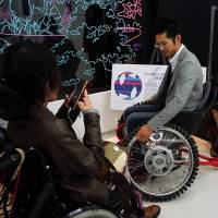 A man tries out a wheelchair that can also move sideways at Super Welfare Expo on Nov. 10 in Tokyo's Shibuya Ward. | MAGDALENA OSUMI