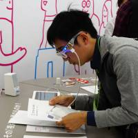 A man tries Oton Glass smart glasses that read out text for the visually impaired and those with dyslexia. The glasses provide translations in Japanese and English. | MAGDALENA OSUMI