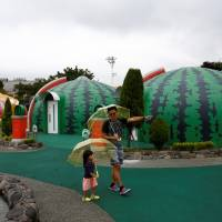 A family from Singapore takes a walk around quake-resistant dome houses. | REUTERS