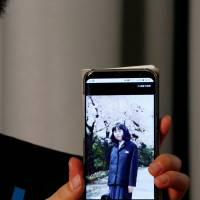 Takuya Yokota displays a picture of his sister Megumi Yokota, who was abducted by North Korean agents decades ago as a schoolgirl, on his smartphone during an interview in Tokyo on Oct. 26. | REUTERS