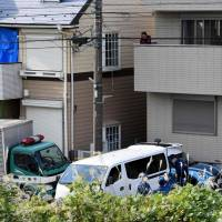 A man watches police gather in front of an apartment in Zama, Kanagawa Prefecture, where nine bodies were discovered on Oct. 31. | AFP-JIJI