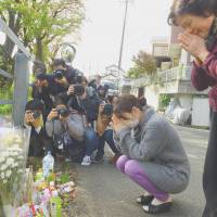 Neighbors pray Friday in front of flowers on a street near the apartment in Zama, Kanagawa Prefecture, where the dismembered bodies of nine young people were found late last month. | KYODO