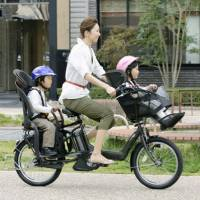 A woman carries two children on an electric bicycle. | KYODO