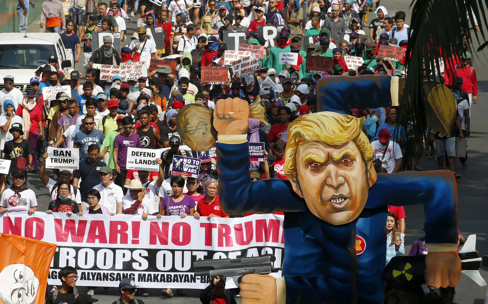 Protesters march in a rally against the visit of U.S. President Donald Trump on Monday in Manila, where ASEAN leaders and their dialogue partners are meeting for two days to discuss issues facing the region, including the South China Sea.   AP