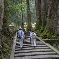 Walk this way: Pilgrims dressed in white make their way through the mortuary forest of Okunoin in Wakayama Prefecture. | STEPHEN MANSFIELD
