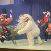White devil: Members of the Kuwatatenshi Kagura Troupe take part in a scene depicting a battle between some warriors and a  white fox demon. | COURTESY OF AKITAKATA, HIROSHIMA PREFECTURE