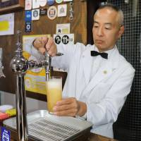 Labor of love: Beer Stand Shigetomi opens only two hours a day in the corner of a liquor store and serves customers only two drinks max. 'I want a restaurant in Hiroshima to one day be able to serve better beer than I do, which would mean I could fulfill my dream of devoting myself to the liquor shop,' says owner Yutaka Shigetomi. | KYODO