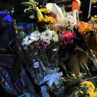 Remembered: Flowers accumulate outside the apartment in Zama, Kanagawa Prefecture, in which nine people were found murdered. | KYODO