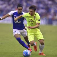 Urawa's Tsukasa Umesaki (right) moves the ball away from Al-Hilal's Mohamed Kanno during the Asian Champions League final first leg in Riyadh on Nov. 18. | AP