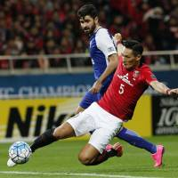 Urawa Reds defender Tomoaki Makino intercepts the ball ahead of Al Hilal striker Omar Khrbin during the second leg of the Asian Champions League final at Saitama Stadium on Saturday. Urawa won the match 1-0 to claim the title 2-1 on aggregate. | AP