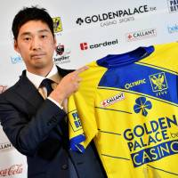 Sint-Truiden board member Yusuke Muranaka holds up a uniform after a news conference on Wednesday in Limburg, Belgium. | AFP-JIJI