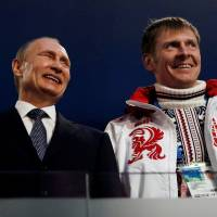 Russian President Vladimir Putin (left) laughs with gold medal-winning bobsled athlete Alexander Zubkov during the closing ceremony for the Sochi Games on Feb. 23, 2014. | REUTERS