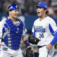 BayStars pitcher Haruhiro Hamaguchi (right) and catcher Shuto Takajo react after the third inning of Game 4 of the Japan Series on Wednesday in Yokohama. The BayStars beat the Hawks 6-0. | KYODO