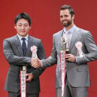 Central League MVP Yoshihiro Maru (left) and Pacific League MVP Dennis Sarfate shake hands at the annual NPB Awards on Monday. | KYODO