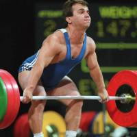 Turkey's Naim Suleymanoglu snatches 147.5 kg on his way to winning his third consecutive Olympic weightlifting gold medal in the featherweight division at the 1996 Atlanta Summer Games. The legendary weightlifter died on Friday at age 50. | AFP-JIJI