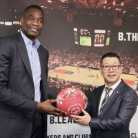 Dikembe Mutombo, a Special Olympics ambassador and former NBA star, holds a special Special Olympics basketball with B. League chairman Masaaki Okawa at the league office on Friday. | KAZ NAGATSUKA