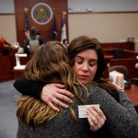 Larissa Boyce (right) gets a hug from Alexis Alvarado, both victims of Larry Nassar, during a hearing in Ingham County Circuit Court on Wednesday in Lansing, Michigan. Former USA Gymnastics team doctor Lawrence (Larry) Nassar, accused of molesting dozens of female athletes over several decades, on Wednesday pleaded guilty to multiple counts of criminal sexual conduct. | AFP-JIJI
